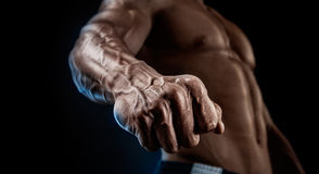 Close-up of athletic muscular arm and torso. Handsome muscular bodybuilder demonstrates his fist and vein, blood vessels. Studio shot on black background Royalty Free Stock Photography