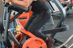 Close up athletic muscular man doing abs exercise. On abdominal coaster gym machine Royalty Free Stock Photo