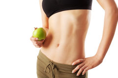 Close up of athletic woman belly holding a green apple in hand. Isolated on white Royalty Free Stock Photos