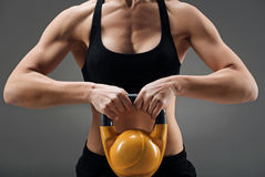 Close up of athletic woman demonstrating gym weight. Be powerful. Close up of athletic young strong woman demonstrating gym weight while training and posing on a Stock Photos