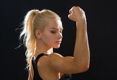 Close up of athletic woman flexing her biceps Royalty Free Stock Images