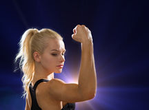 Close up of athletic woman flexing her biceps Royalty Free Stock Image
