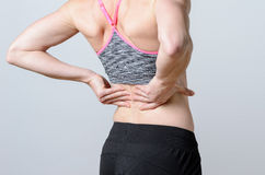 Close up Athletic Woman Holding her Injured Back stock images