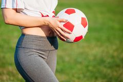 Close-up athletic young girl on football field with ball on a sunny summer day with his back to camera stock photos