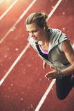 Close-up of athletic young woman running fast on stadium. Close-up of athletic young sportswoman running fast on track field while listening to music Royalty Free Stock Image