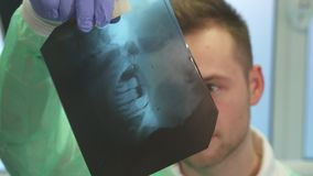 Dentist looks at x-ray. Close up attractive blond dentist looking at x-ray. Young caucasian dental specialist examining teeth on the image. Camera alternately Royalty Free Stock Photography