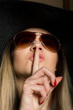 Close-up of attractive brunette woman in a bikini, big hat and sunglasses putting a finger on her lips Royalty Free Stock Photography
