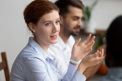 Close up attractive businesswoman sitting and talking to colleague. Woman sharing business ideas, answering questions. Diverse coworkers on meeting, seminar royalty free stock image