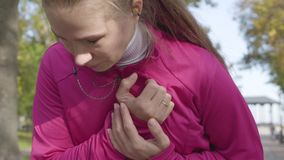 Close-up of an attractive Caucasian woman in pink sportswear having chest pain. Female runner feeling bad during the. Morning training in the autumn park stock video footage