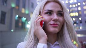 Close-up of attractive confident woman in white jacket talking by cell phone standing on the city street. Businesswoman. Close-up of attractive confident woman stock video footage