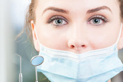 Close up attractive dentist face with tools and mask Royalty Free Stock Photography