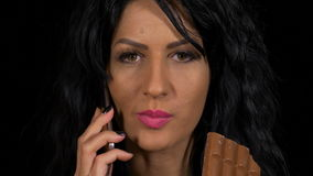 Close-up of attractive female chatting at smartphone while eating a chocolate stock video