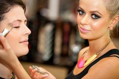 Close up of attractive female make up artist at work. Stock Photography