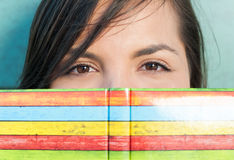 Close-up of attractive girl hiding behind agenda or notebook Royalty Free Stock Photography