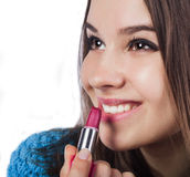 Close up of an attractive girl she opened her mouth and put them red lipstick. Smiles. Brown eyes. Stock Image