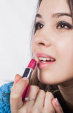 Close up of an attractive girl she opened her mouth and put them red lipstick. Smiles. Brown eyes. Stock Photos