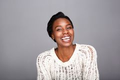 Close up attractive laughing black woman in white sweater. Close up portrait of attractive laughing black woman in white sweater royalty free stock image