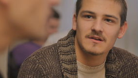 Close-up - attractive man with mustache talking with friend in a bar. Close-up, camera focuses on a face of attractive man. Smiling man looks on his friend and stock video footage