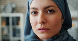 Close-up of attractive Middle Easter lady in hijab looking at camera in office. Close-up of attractive Middle Easter lady in hijab looking at camera standing in stock video footage