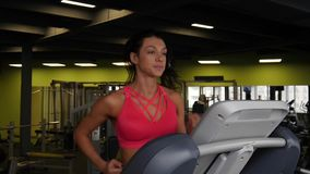 Close up of attractive mixed race woman running on the treadmill in the sport gym. Close up of attractive mixed race woman running on the treadmill in the sport stock video