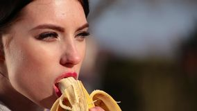 Close-up attractive young brunette woman with beautiful eyes and red lips eats banana on sunny day. Spring beriberi, vitamins in fruits stock video footage
