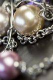 Close up of attractive shiny beads. Close up of three attractive shiny purple beads attached by silver chains on an item of jewellery in a fashion and handicraft Stock Image