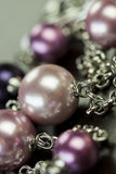 Close up of attractive shiny beads. Close up of three attractive shiny purple beads attached by silver chains on an item of jewellery in a fashion and handicraft Stock Images