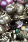 Close up of attractive shiny beads. Close up of three attractive shiny purple beads attached by silver chains on an item of jewellery in a fashion and handicraft Stock Photo