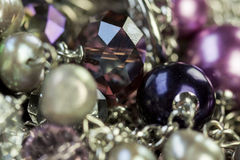 Close up of attractive shiny beads. Close up of three attractive shiny purple beads attached by silver chains on an item of jewellery in a fashion and handicraft Stock Photography
