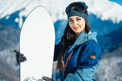 Close up of snowboard girl smiling and posing on mountain and slope background. royalty free stock photography