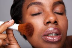 Close up attractive woman applying makeup with brush for beautiful complexion. Close up portrait of attractive woman applying makeup with brush for beautiful royalty free stock photos