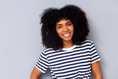 Close up attractive young african woman smiling against gray background. Close up portrait of attractive young african woman smiling against gray background Stock Photo