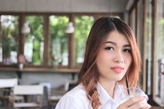 Close up attractive young Asian woman holding coffee cup and looking to camera at cafe with copy space background. Stock Photo
