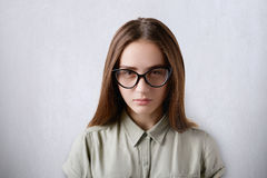 A close-up of attractive young brown-eyed girl with dark straight hair wearing shirt and big glasses isolated over grey background Royalty Free Stock Photos