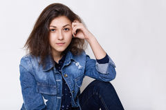 A close-up of attractive young brown-eyed girl wearing jean jacket looking into camera very attentively being confident in herself Royalty Free Stock Photography