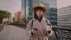 Close-up of attractive young businesswoman walking on urban street and using modern smartphone outside, sunshine, slow stock video footage