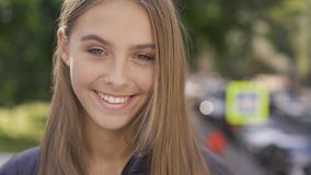 Close-up of attractive young caucasian woman with long brown hair smiling happily looking at camera. Emotions, happiness. Good mood concept stock footage