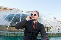 Close up attractive young man talking on the phone near a fountain Royalty Free Stock Photo