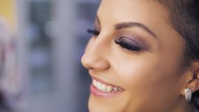 Close-up of attractive young woman with beautiful makeup smiling at camera. Slowmotion shot stock video footage