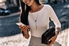 Chating with friends. Close-up of attractive young woman holding smart phone and smiling while standing outdoors stock image