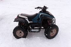 Close-up ATV 4wd quad bike in forest at winter 4wd all-terreain vehicle stand in heavy snow with deep wheel track. Seasonal stock images