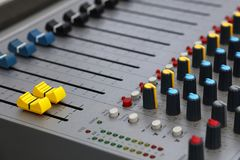 Close up audio control sound mixing console. Board with fader bars, buttons and sliders, high angle view royalty free stock photos