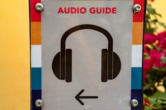 Close up audio guide sign. Closeup image of plate with audio guide sign in museum Royalty Free Stock Photography