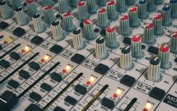 Close-up of audio mixing desk with knobs and sliders stock photo