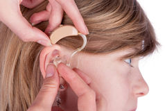 Close up of an Audiologist hands inserting a hearing aid into ea. Close up of an ear and hands inserting a hearing aid into ear. Studio shot isolated on white Stock Images