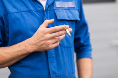Close up of auto mechanic smoking cigarette Royalty Free Stock Photo