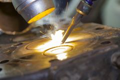 Close up automobile engine head cylinder repair or modify by welder with laser welding method.  stock photos