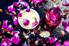 Close up of ayurvedic and beneficial face pack for dull and black skin i.e. Face pack of Rose water with gram flour and some rosa. Petals on wooden surface stock photos