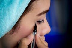 Close-up Aziatische vrouw die eyeliner op oog toepassen stock afbeeldingen
