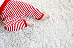 Close-up of baby body and legs in red Santa Clause trousers on Christmas Stock Image
